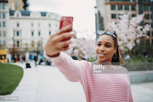Young Nigerian woman taking selfie in city downtown