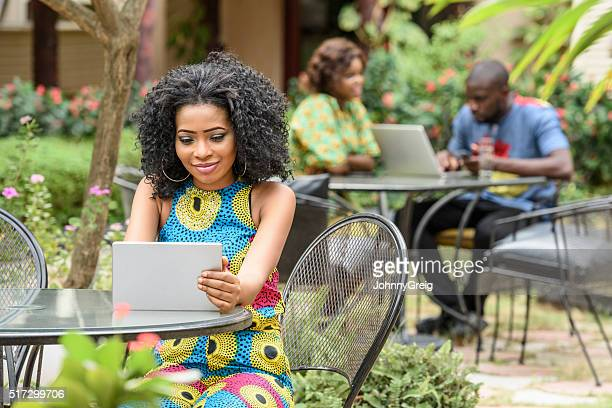 Young Nigerian woman using tablet in cafe