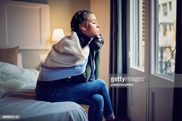 Joven nostálgica está mirando por la ventana en la mañana