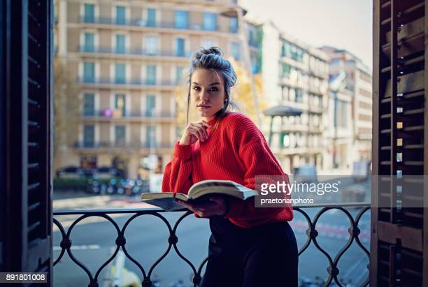 Young nostalgic girl is reading book at the balcony