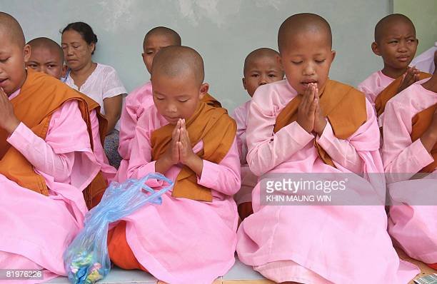 Young novice Buddhist nuns pray at the famous Shwedagon Pagoda in downtown Yangon as they recite religious verses on July 17 2008 to mark the day...