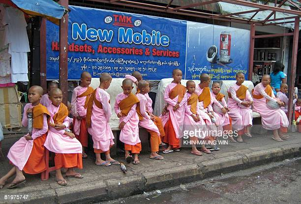 Young novice Buddhist nuns wait at a bus stop in downtown Yangon on July 17 2008 Buddhists around the region have been marking the festival of Asalha...