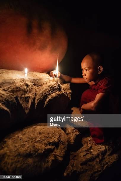 Young Novice Monk Lighting Candles in Buddhist Temple