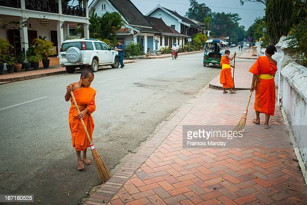 Young novice monks brushing off the streets of Luang Prabang with brooms in front of the Wat Sen temple after the morning alms.