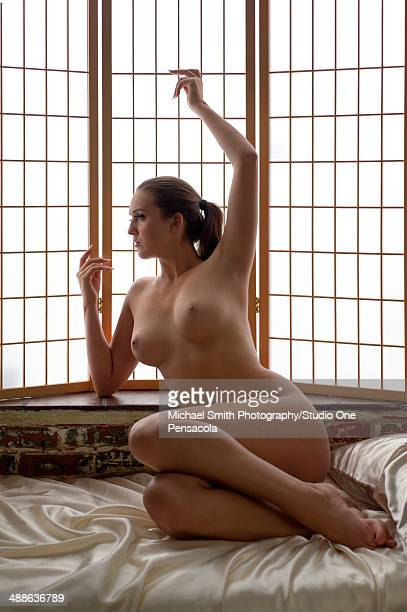 young nude female looking out a bay window - erker stockfoto's en -beelden