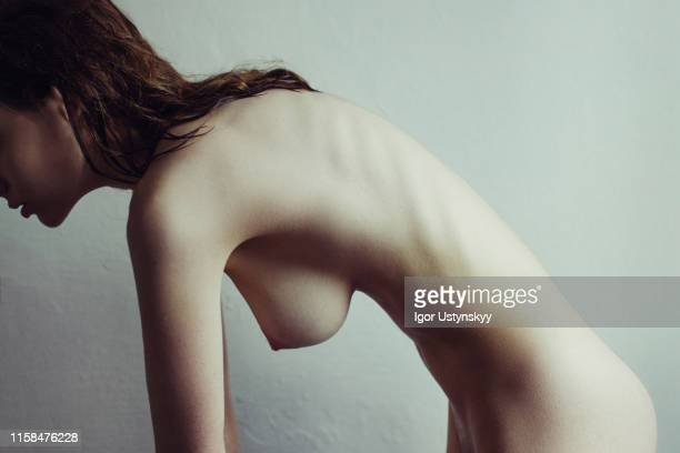 young nude woman bending against white background - femme maigre photos et images de collection