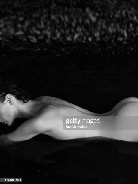 young nude woman lying in dark water - naturists stock pictures, royalty-free photos & images