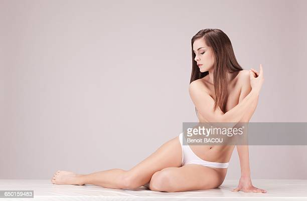 Young nude woman sitting on the floor in profile, eyes closed