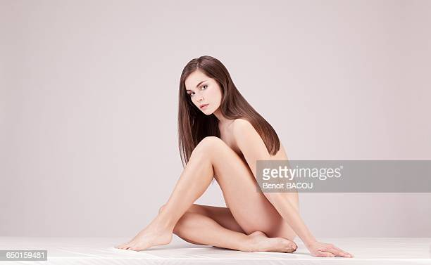 Young nude woman sitting on the ground in profile, looking toward the lens