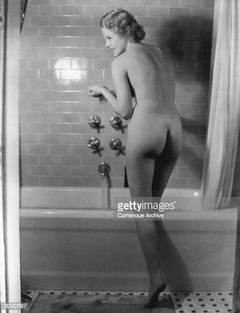 A young nude woman steps into a bathtub filling with water