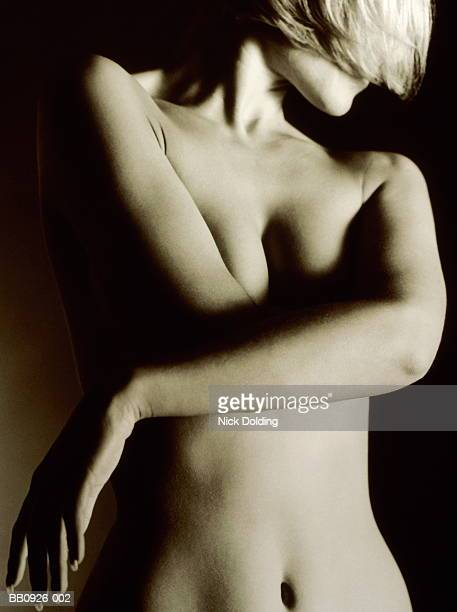 young nude woman with arms crossed in front of breasts,portrait (b&w) - mulher nua no escuro imagens e fotografias de stock