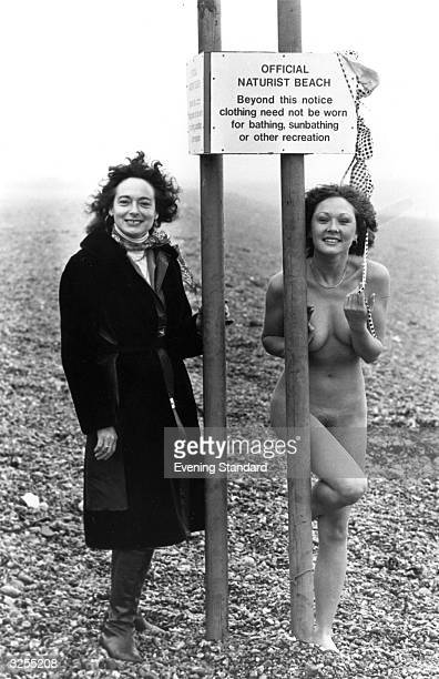A young nudist covers her assets having bravely stripped off for the camera on Brighton's nudist beach Her sensible friend remains fully clothed in...