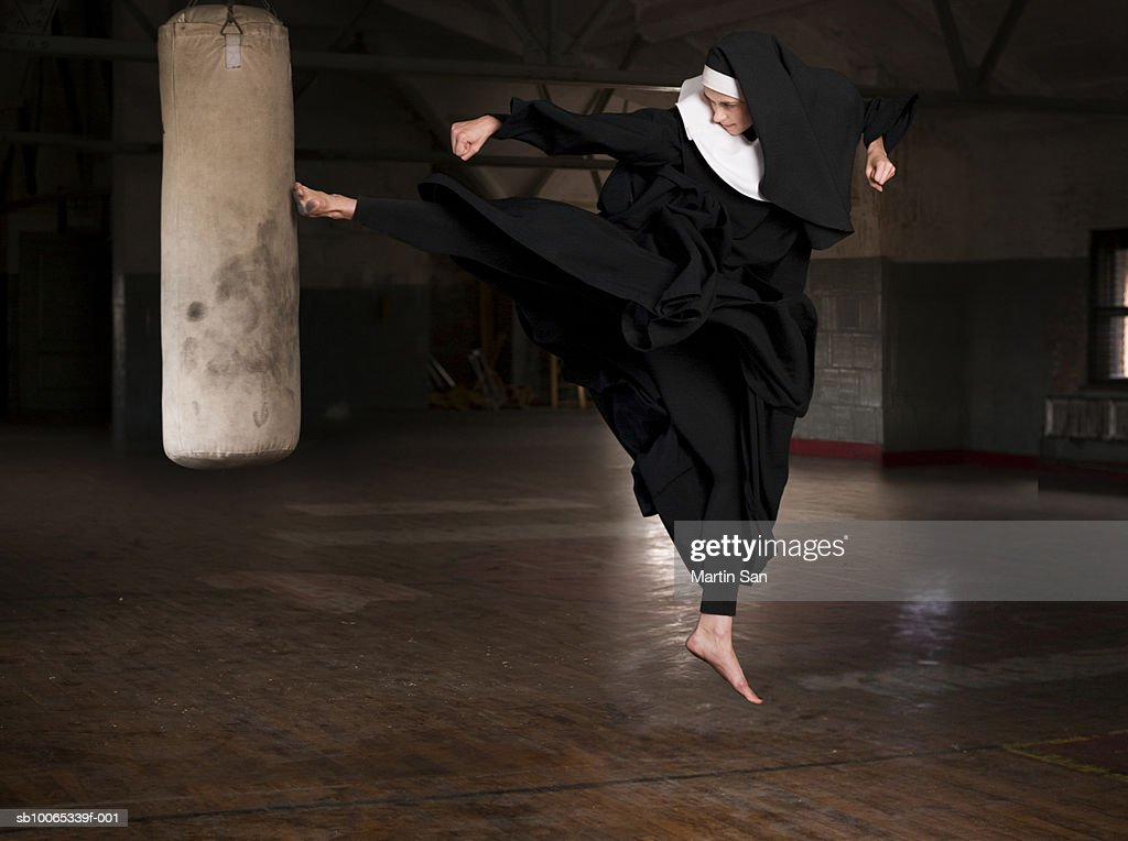 Young nun kicking punch bag in gym : Foto stock