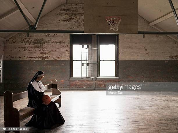 young nun sitting on bench in court holding basketball - 聖職服 ストックフォトと画像