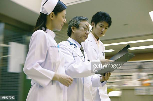 Young nurse and doctor listening to senior doctor