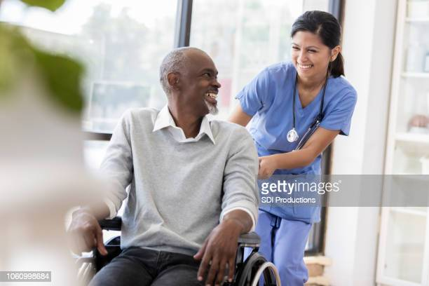 Young nurse and senior patient in a wheelchair smile at each other