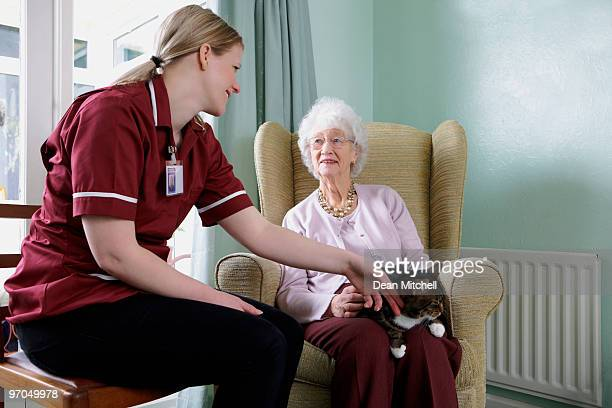 Junge Krankenschwester und senior Frau streicheln die Katze Pflege zu Hause in