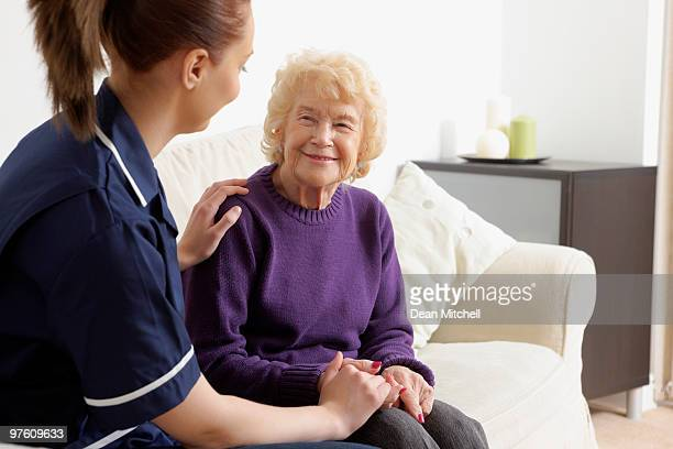 Young nurse assisting a happy senior woman