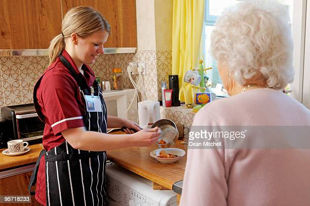 young Nurse cooking for senior woman in her kitchen