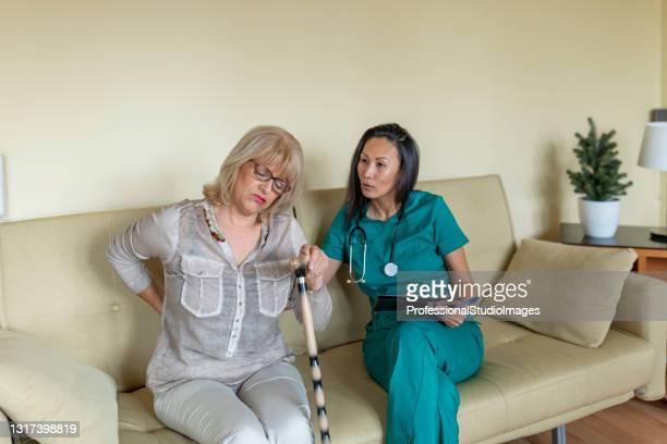緑の制服を着た若い看護師は、背中の痛みを持つ彼女の先輩患者と話しています。 - 下背部痛 ストックフォトと画像