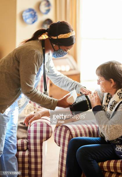 young nurse taking a senior patient's blood pressure during a home visit - infectious disease stock pictures, royalty-free photos & images
