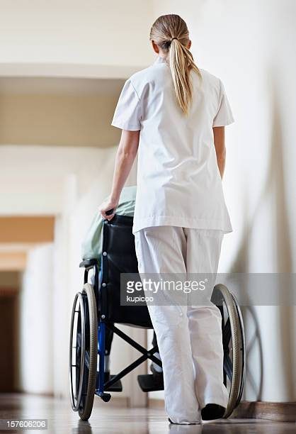 Young nurse taking  patient in a wheelchair