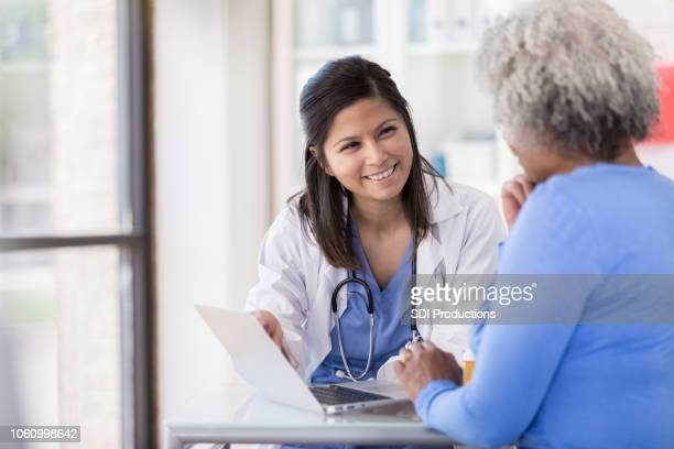 young nurse uses laptop while sitting with senior patient - doctor and patient stock pictures, royalty-free photos & images