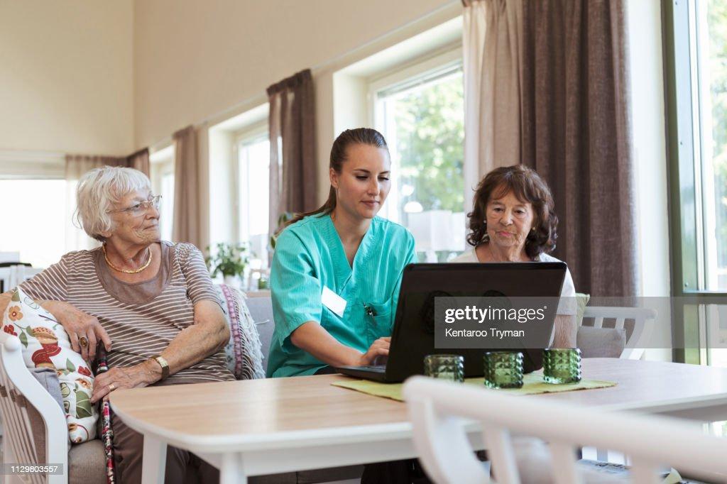 Young nurse using laptop while sitting amidst senior women at nursing home : Stock Photo