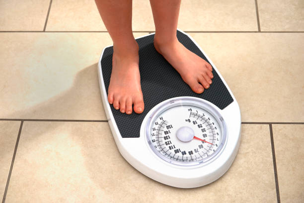 young obese boy on bathroom scales - weight loss stock pictures, royalty-free photos & images