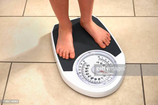 young obese boy on bathroom scales - mass unit of measurement stock pictures, royalty-free photos & images