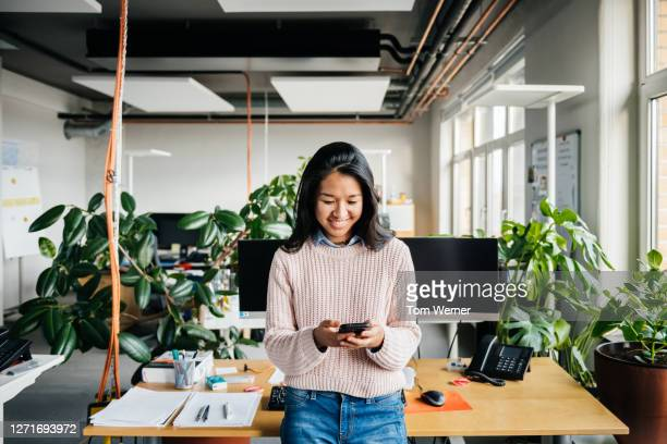 young office employee using smartphone at desk - employee stock pictures, royalty-free photos & images