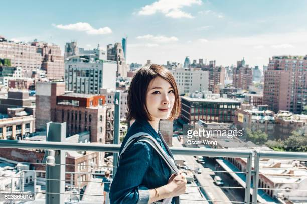 young office lady looking out to new york cityscape, on rooftop - 若い女性一人 ストックフォトと画像