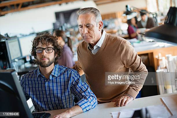 Young office worker assisted by elder colleague