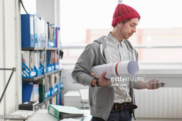 young office worker holding plans and using mobile phone in creative office - design professional stock pictures, royalty-free photos & images