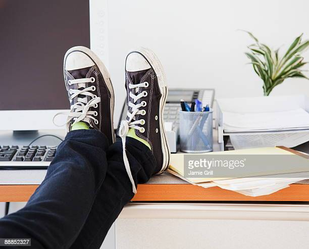 Young office worker in casual clothes relaxing in office with legs on desk