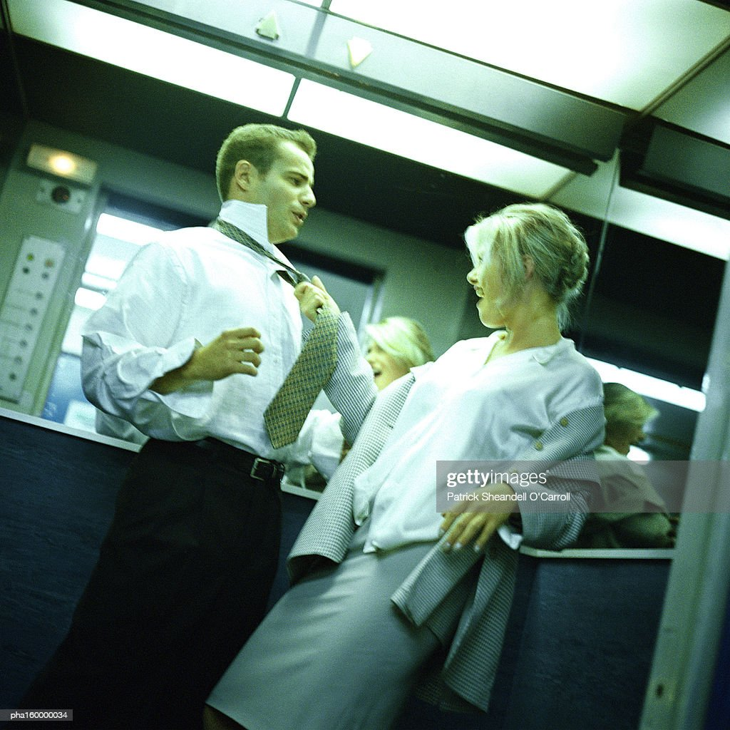 Young office worker pulling colleague toward her by his tie. : Stockfoto