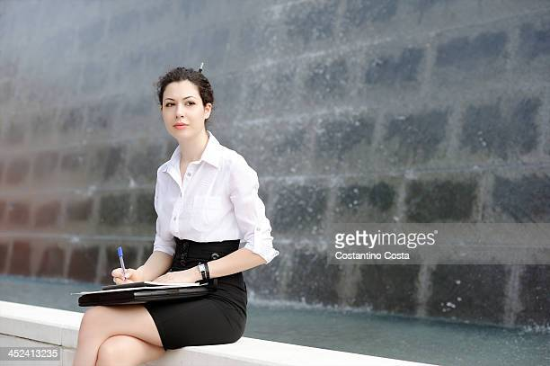 young office worker sitting on bench with files - white skirt stock pictures, royalty-free photos & images