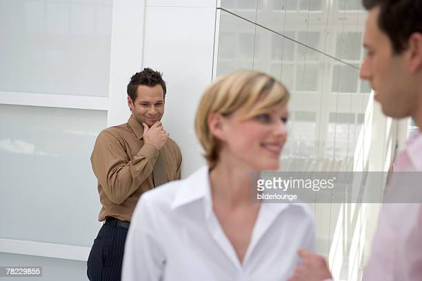 young office worker smiling behind the back of woman engaged in conversation with colleague