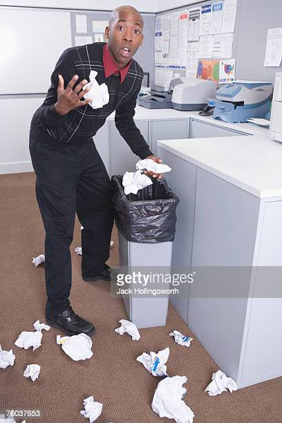 Young office worker throwing away crumpled papers from trash can, portrait