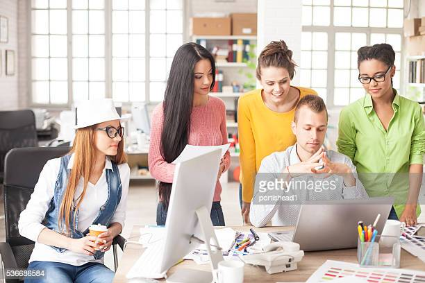 Young office workers discussing creative ideas at workplace