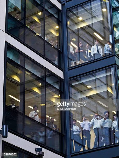 Young office workers onlooking a student protest from a modern glass skyscaper. The protest was against the trebling of university fees that had...