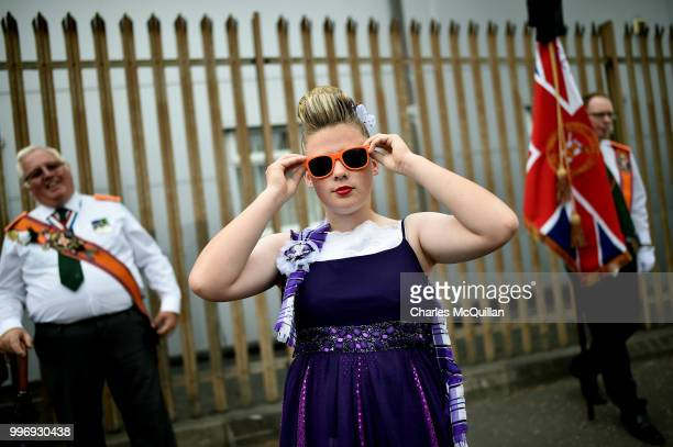 A young Orange band member adjusts her sunglasses as she watches on during the annual 12th of July Orange march and demonstration takes place on July...