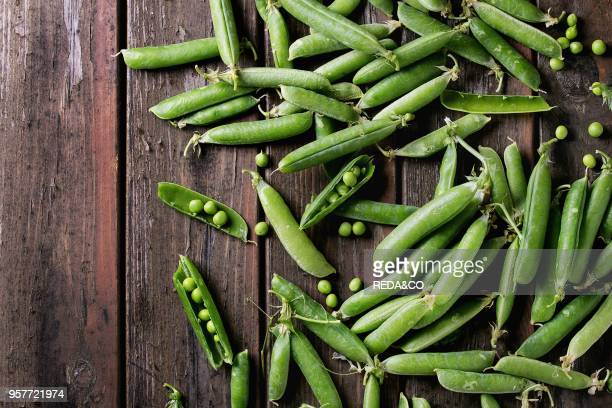 Young organic green pea pods and peas over old dark wooden planks background Top view with space Harvest healthy eating