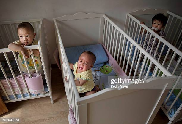 Young orphaned Chinese children are seen in cribs at a foster care center on April 2, 2014 in Beijing, China. China's orphanages and foster homes...