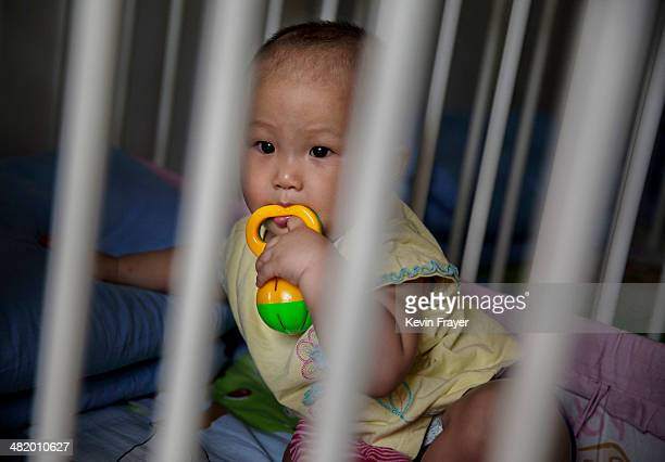 Young orphaned Chinese girl sits in a crib at a foster care center on April 2, 2014 in Beijing, China. China's orphanages and foster homes used to be...