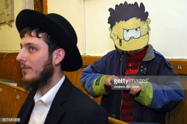 A young Orthodox Jewish boy dressed as Dennis the menace in the congregation during the Megillah reading for Purim in Walford road synagogue Purim is...