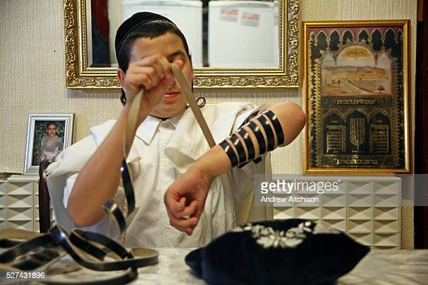 A young Orthodox Jewish boys preparing to pray by wrapping the leather strap of his Tefillin around his arm and a Tallit around his shoulders The...