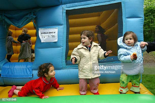 Young Orthodox Jewish girls play on a bouncy castle at a community event in Allen Gardens, Stamford Hill to celebrate Lag B'omer. Women and Men are...