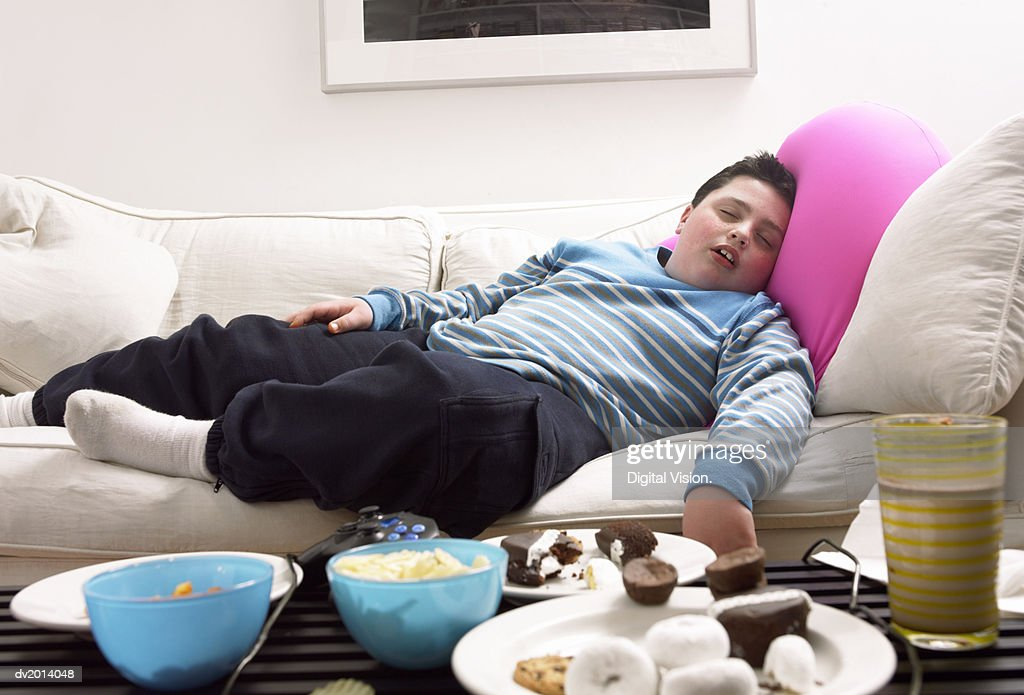 Young, Overweight Boy Sleeps on a Sofa Next to a Table of Crisps and Biscuits : Stock Photo
