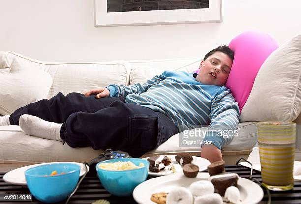 young, overweight boy sleeps on a sofa next to a table of crisps and biscuits - unhealthy living stock pictures, royalty-free photos & images